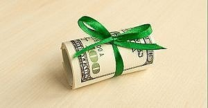 money rolled up with green ribbon
