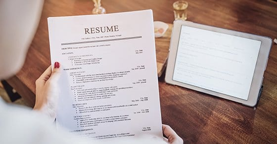 woman holding pen over resume application with smart phone and using computer laptop to job search on online internet. applying for a job concept.