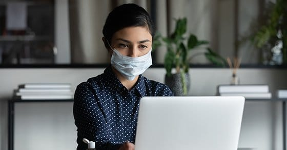 Concentrated young female indian professional wearing breath protective mask, working on computer after washing hands with antiseptic liquid, preventing spreading coronavirus infection in office.